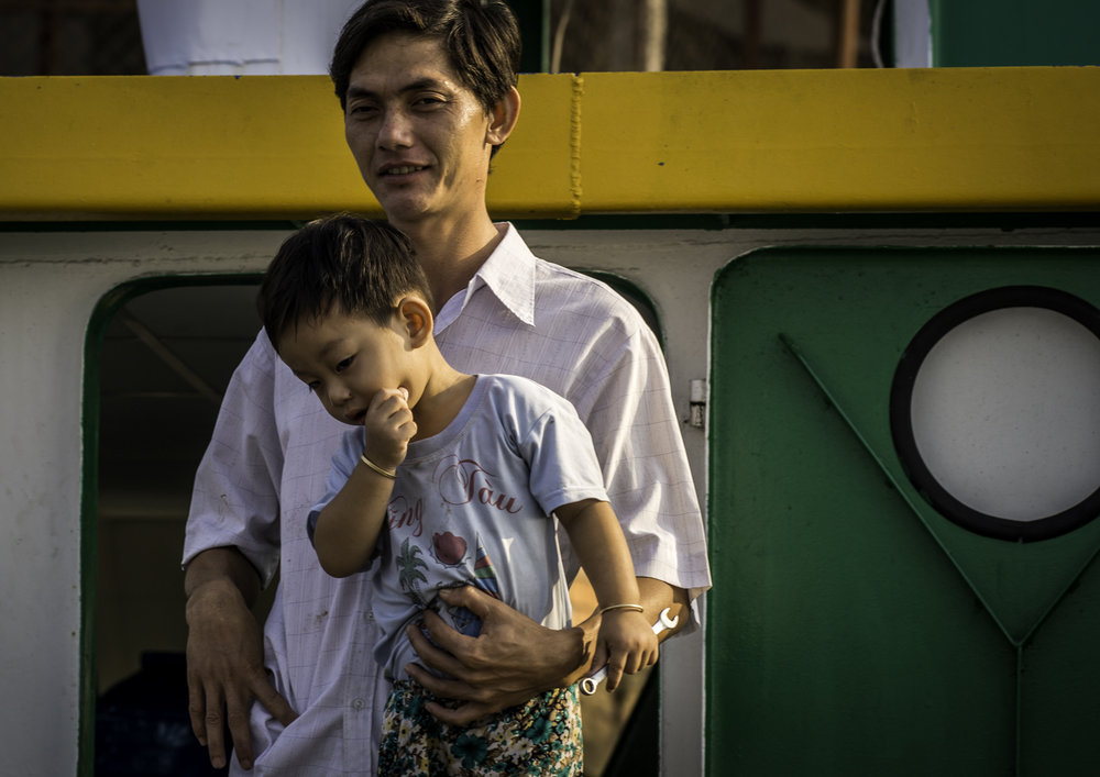 This man, his wife and his young son live on a big commercial boat along Mekong river.