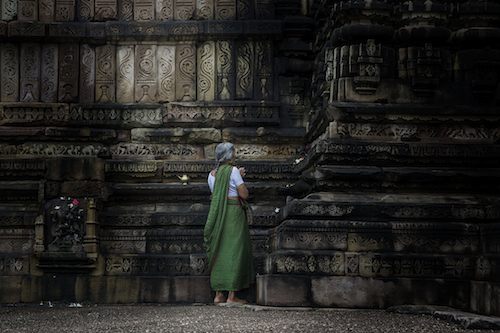 A lady is praying at a Temple in  Khajuraho.