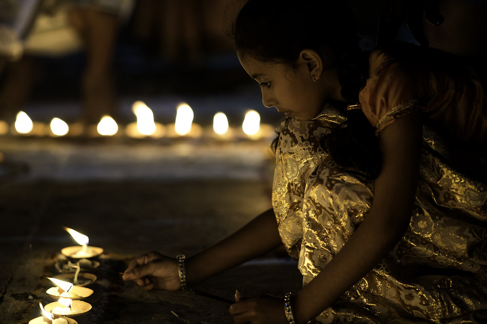 A young girl is lighting candles for the evening ceremony with her family on a ghat in Varanasi.