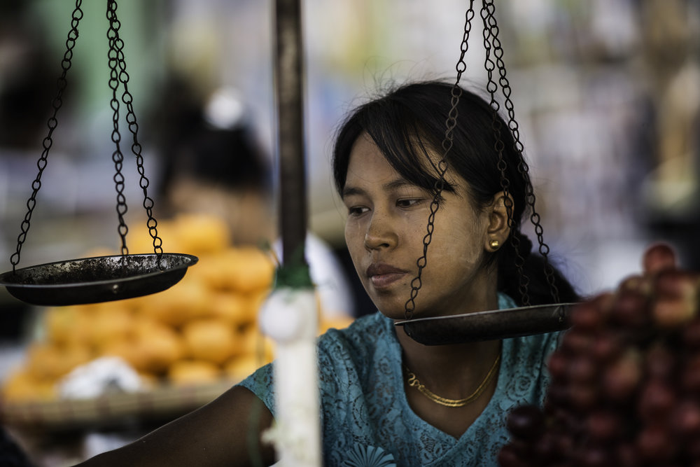 A Burmese girl at her fresh fruits stand.