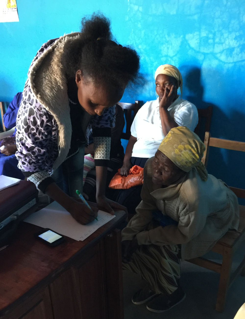 Community Health Worker Emily records the blood pressure of a patient at the outreach clinic.