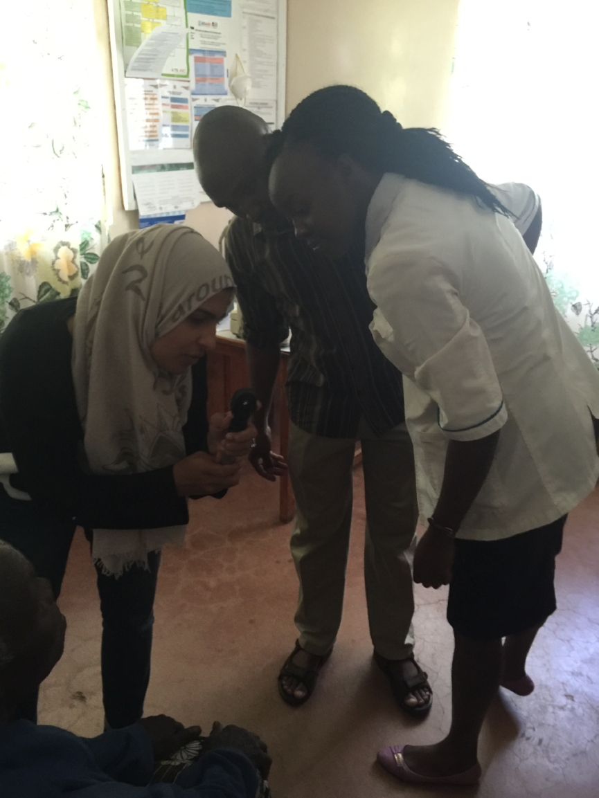 Dr. Sidiqa training Noah and Jemimah on the ophthalmoscop