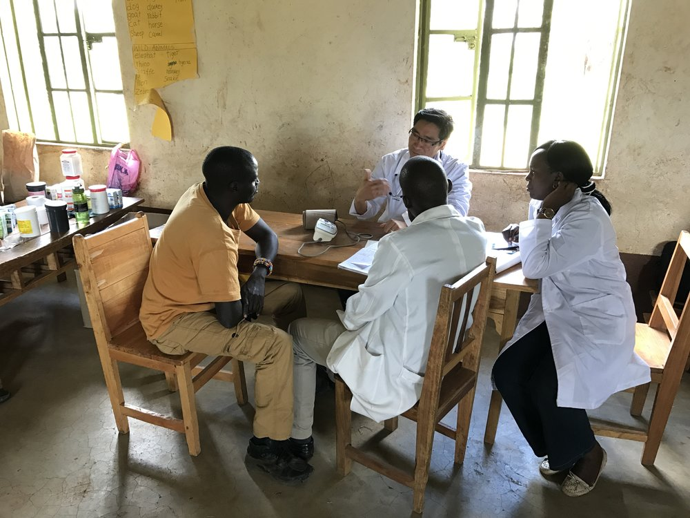 Dr. James working with two of the clinic staff, counselling them on chronic disease care while seeing a patient.