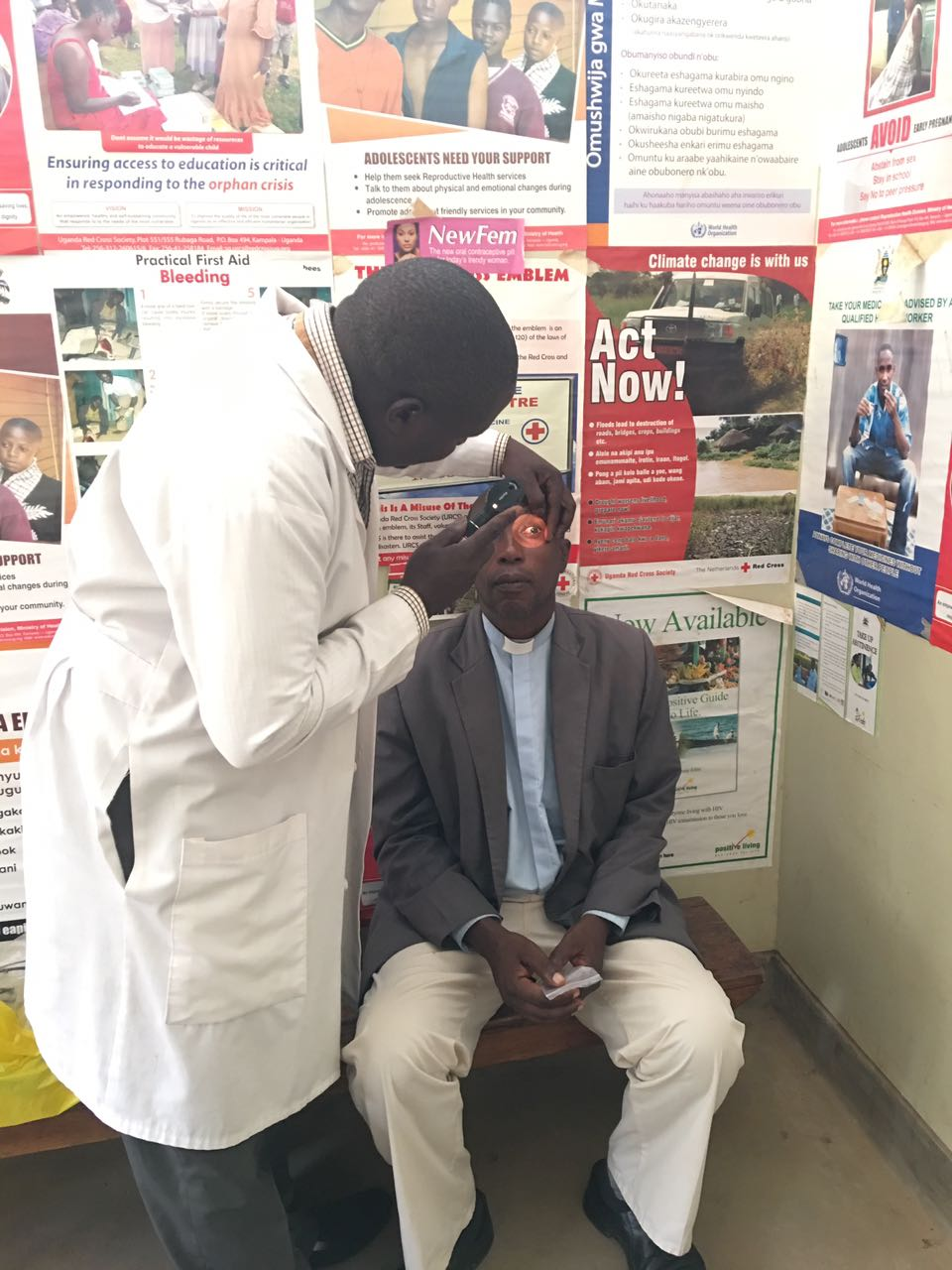 Alex using the ophthalmoscope on a patient to assess his eye health.