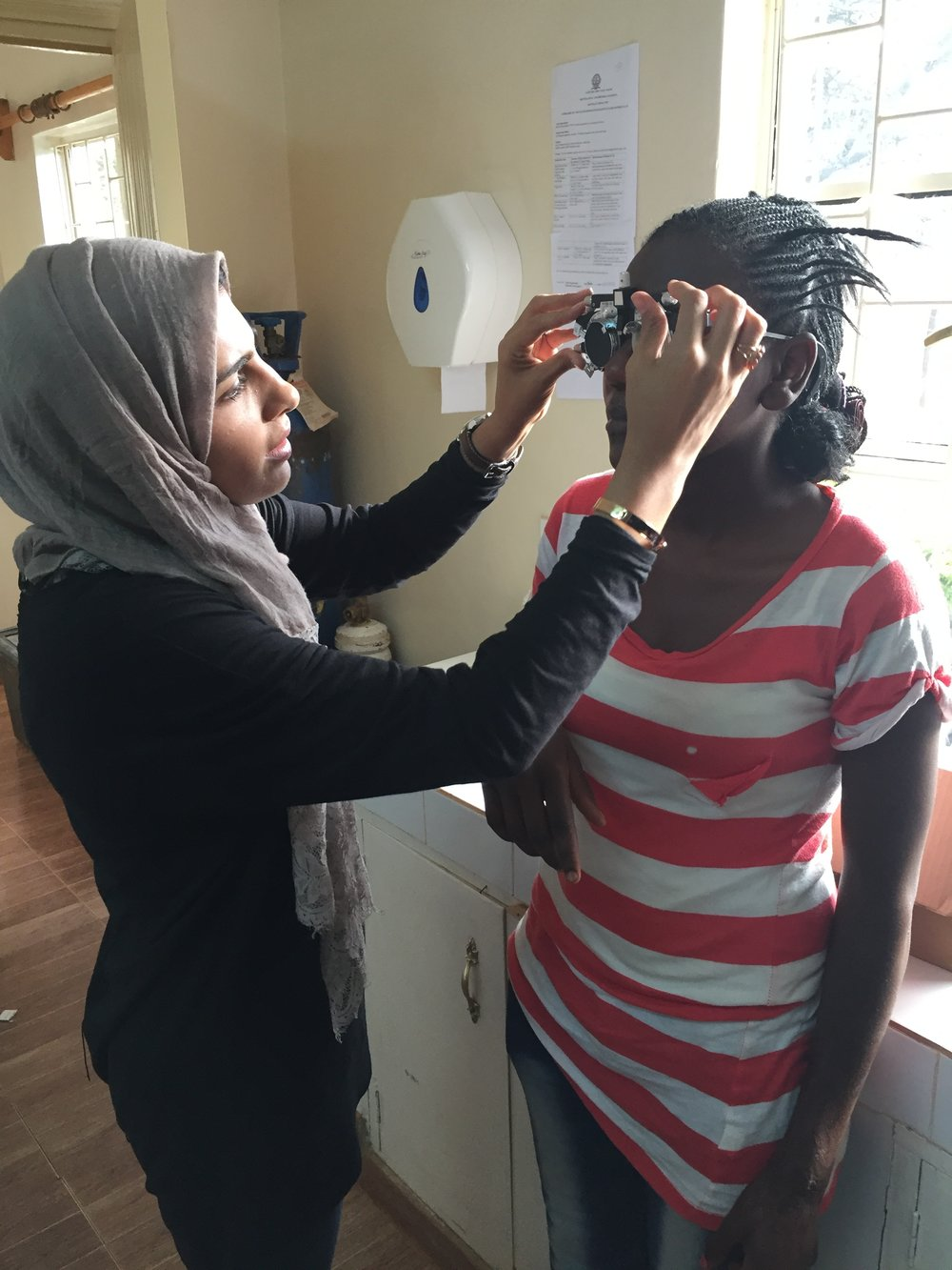 Indoors, Dr. Sidiqa examines patients' eyesight and discusses the Community Health Worker screening program