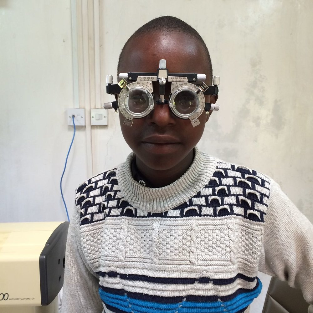 A young patient is fitted with the refractor. A refraction or vision test is as part of a routine eye examination. This test tells the optometrist exactly what prescription may be needed  (February 2018)