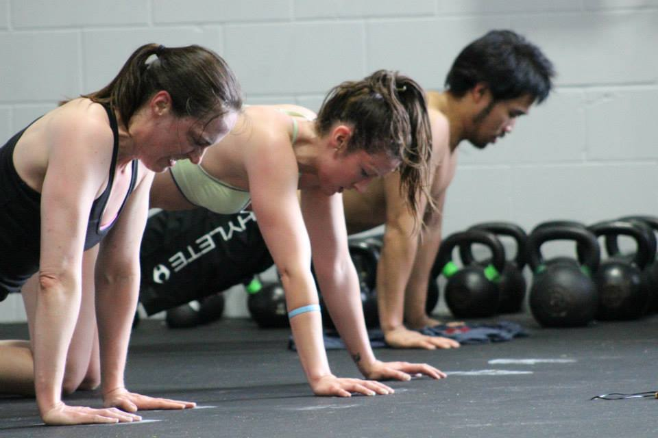 "Clare R., Mary S. and Coach Chris cranking out push-ups during ""Murph"""