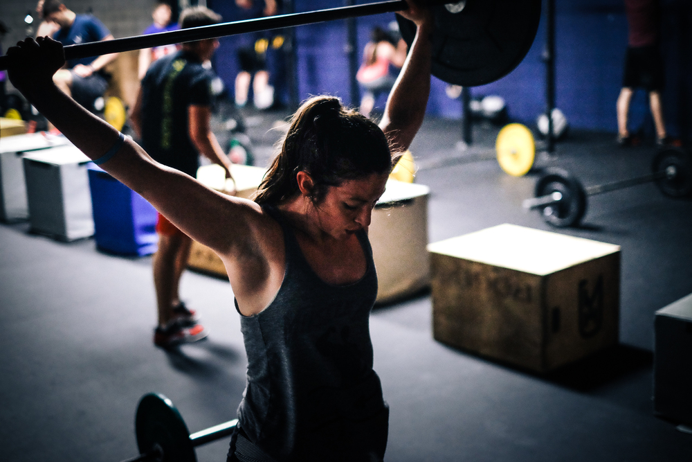 Mary S. standing tall as she finishes a snatch during a workout.