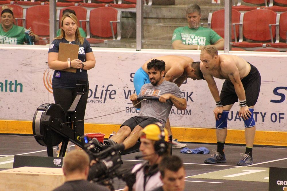 Coach Tony pulling hard on a row during the final event of Granite Games 2015 while his teammates Marcus D. and John Y. look on.