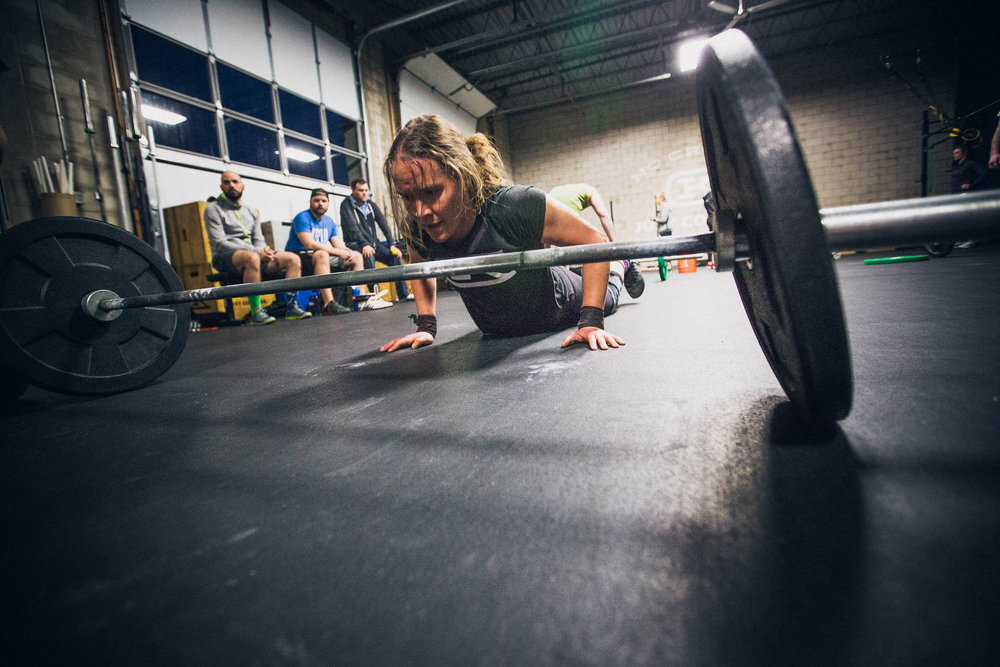 Bar-facing burpees are our favorites. Coach Caitlin finishing a final set during a workout.