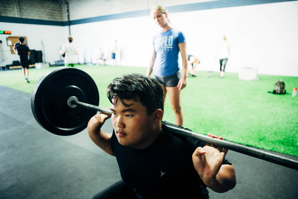 Young or old, everyone should learn how to squat. Learning to squat within their ability, working with their body vastly improves quality of life and longevity...Josh Y. warming up his back squat during CrossFit Teens under the watchful eye of Coach Caitlin.