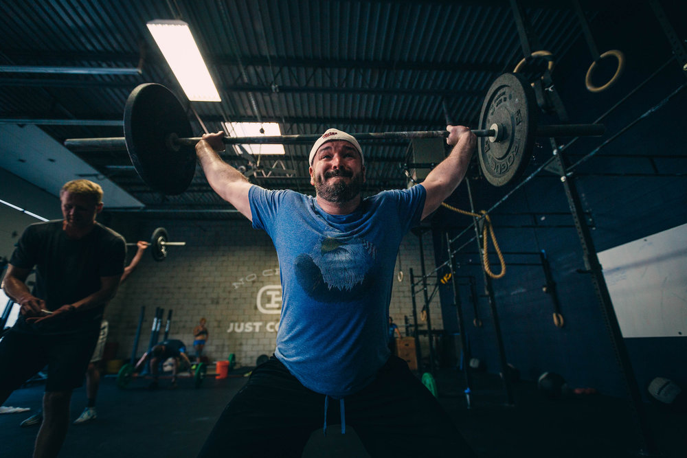 Mike L. locking out a power snatch during a workout. Fight for every rep.