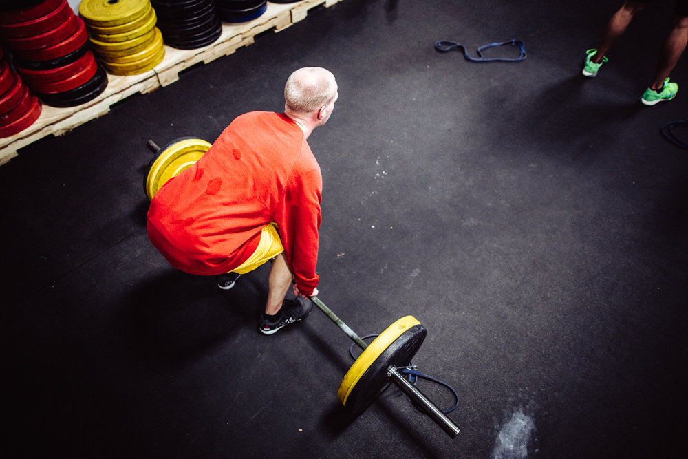 The set-up is critical for success. Whether you're cleaning a barbell or presenting a project at work, how you prepare makes a difference. Tyler A. setting up for a clean mid - workout.