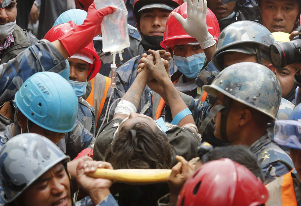 Pemba Tamang clasps the hands of his rescuers after being pulled from the rubble.