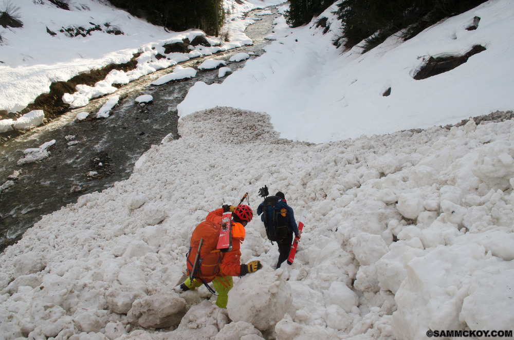 With warm temperatures came significant avalanches. Wet slides often blanket valley slopes. Sometimes debris would bridge entire rivers providing a crossing. Here Steve and Douglas balance on frozen snow boulders next to Mobbs Creek. One of several slide paths full of debris that have come off the north slopes of Mount Bentley.