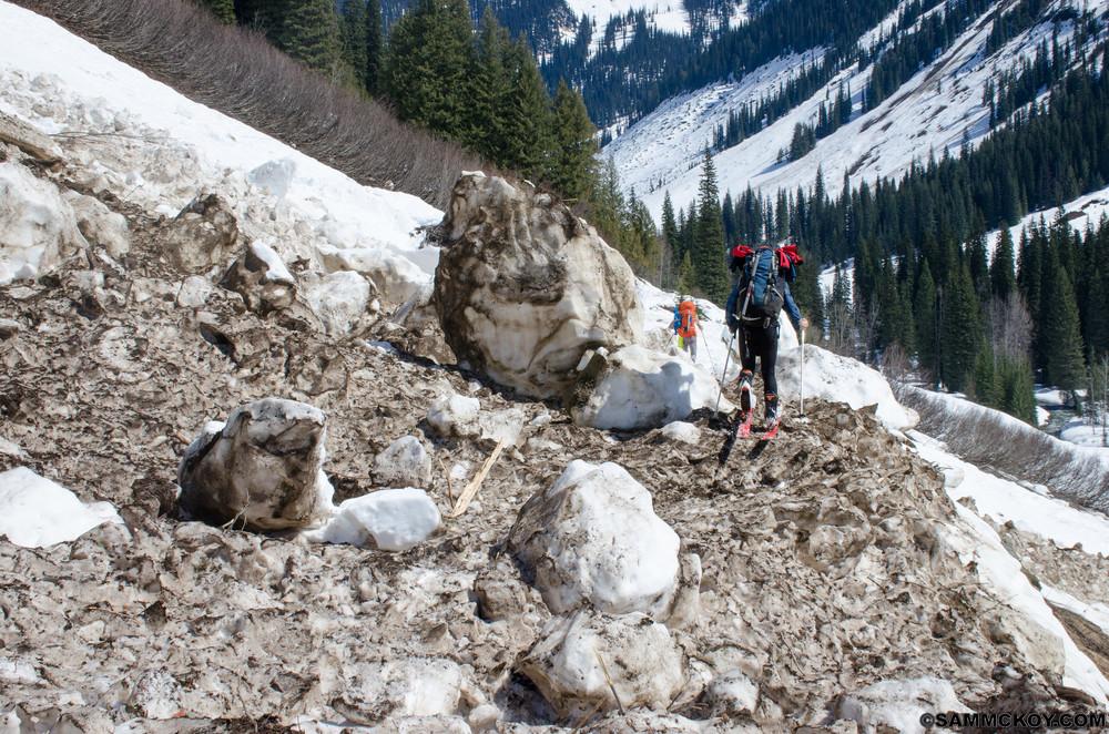 Douglas steps past large piles of avalanche rubble.
