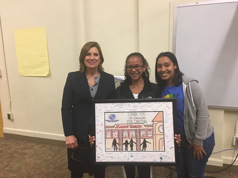 "To thank Glorianne Demoulas and the Demoulas Foundation Staff member Grace Duran and teen member Angie Segura presented her with a drawing they made of the front of the Salem Market Basket Store. Children and staff members signed the art to say ""Thank you for Caring!"""