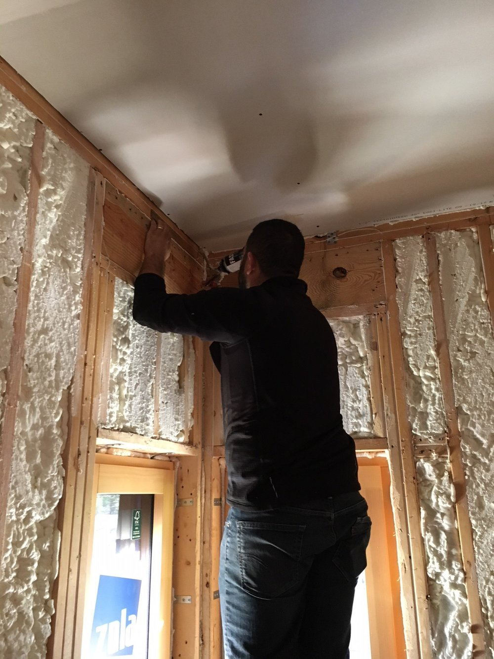 Isaiah Nisos/project manager caulking during blower door test.