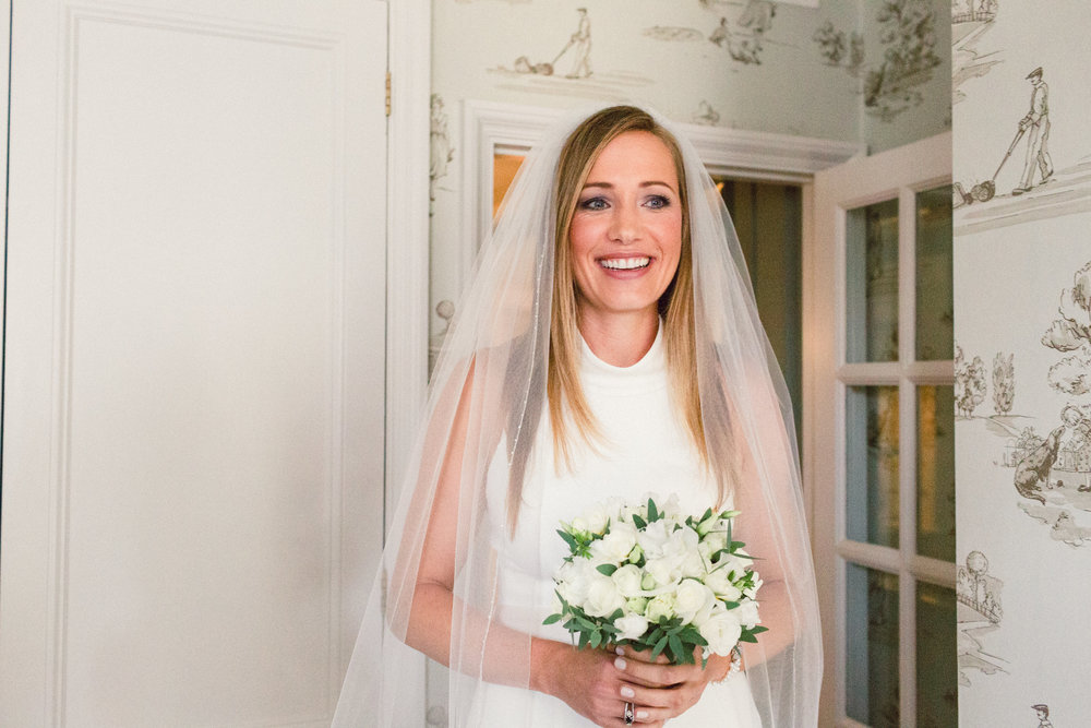 Bride Michelle at Goring Hotel in London - This statuesque stunner favours one particular Mac matt eyeshadow in a gorgeous purple-grey tone, so it was easy to create very flattering, soft, smoky finish. Everything else just fell into place around it, the white pearly smile is the evidence.Photo: Terri Pashley Photography