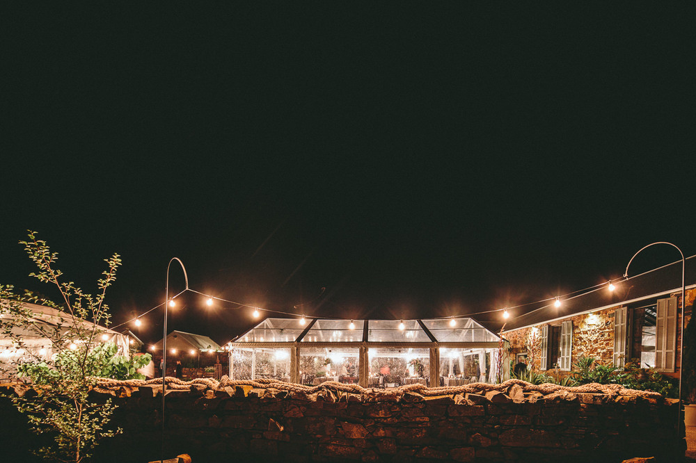 Clear Marquee at night lit by chandeliers and festoon lighting