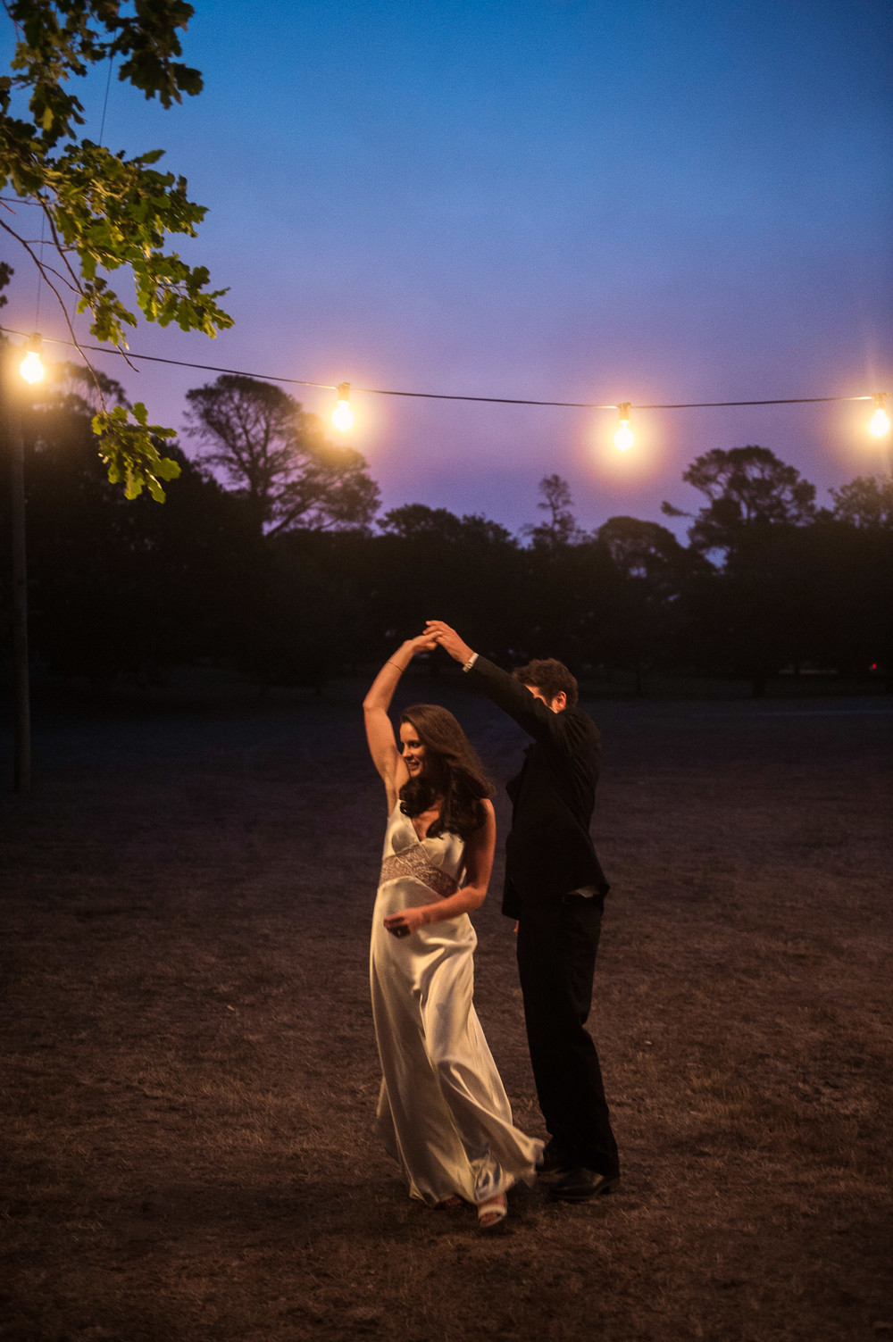 Festoon lighting in the trees surrounding the clear marquee. Bride and groom dancing