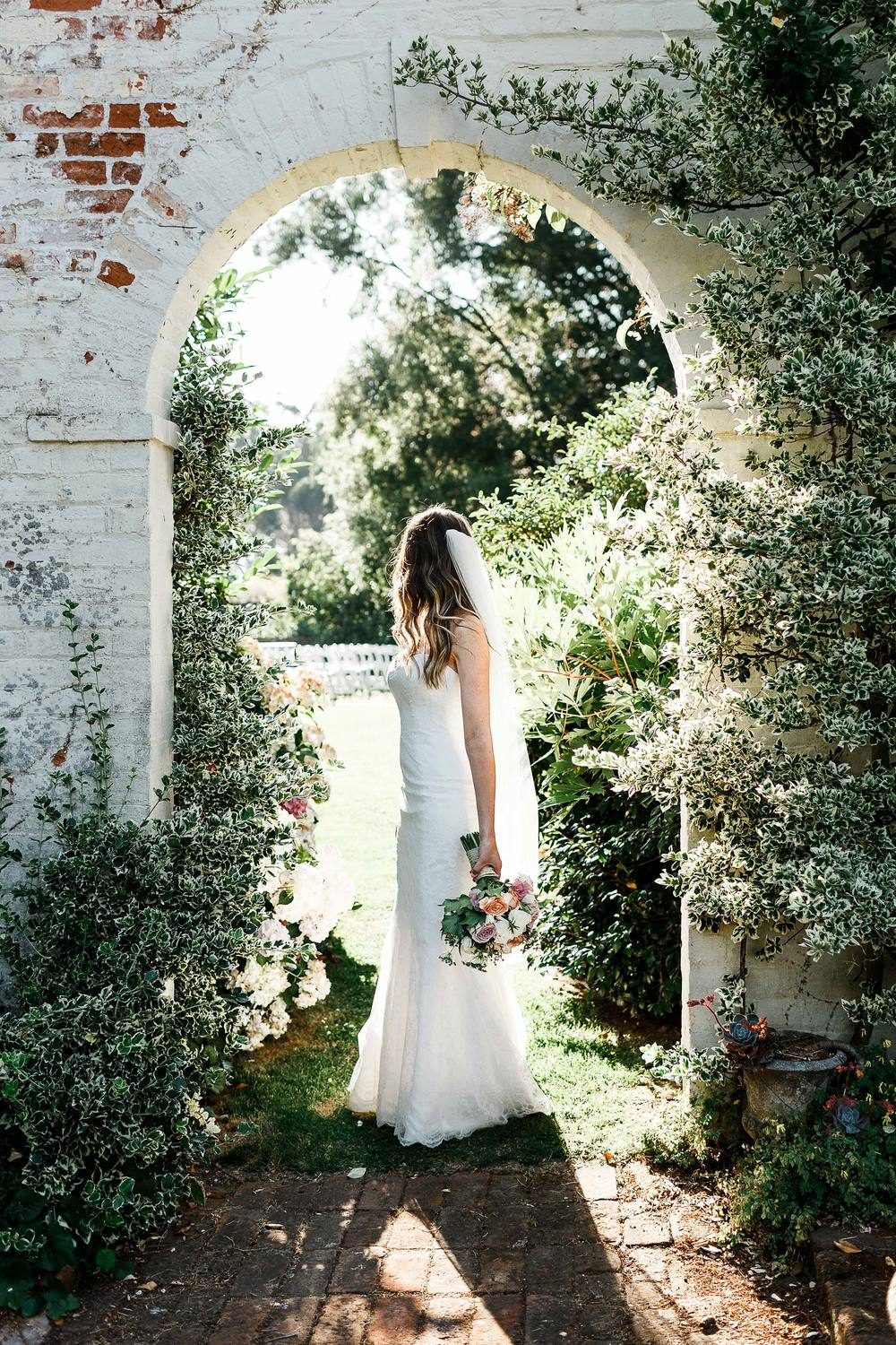 Bride under Brickendon homestead garden arch with bouquet