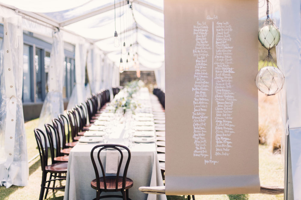 Hand written seating plan for the long table in a clear marquee