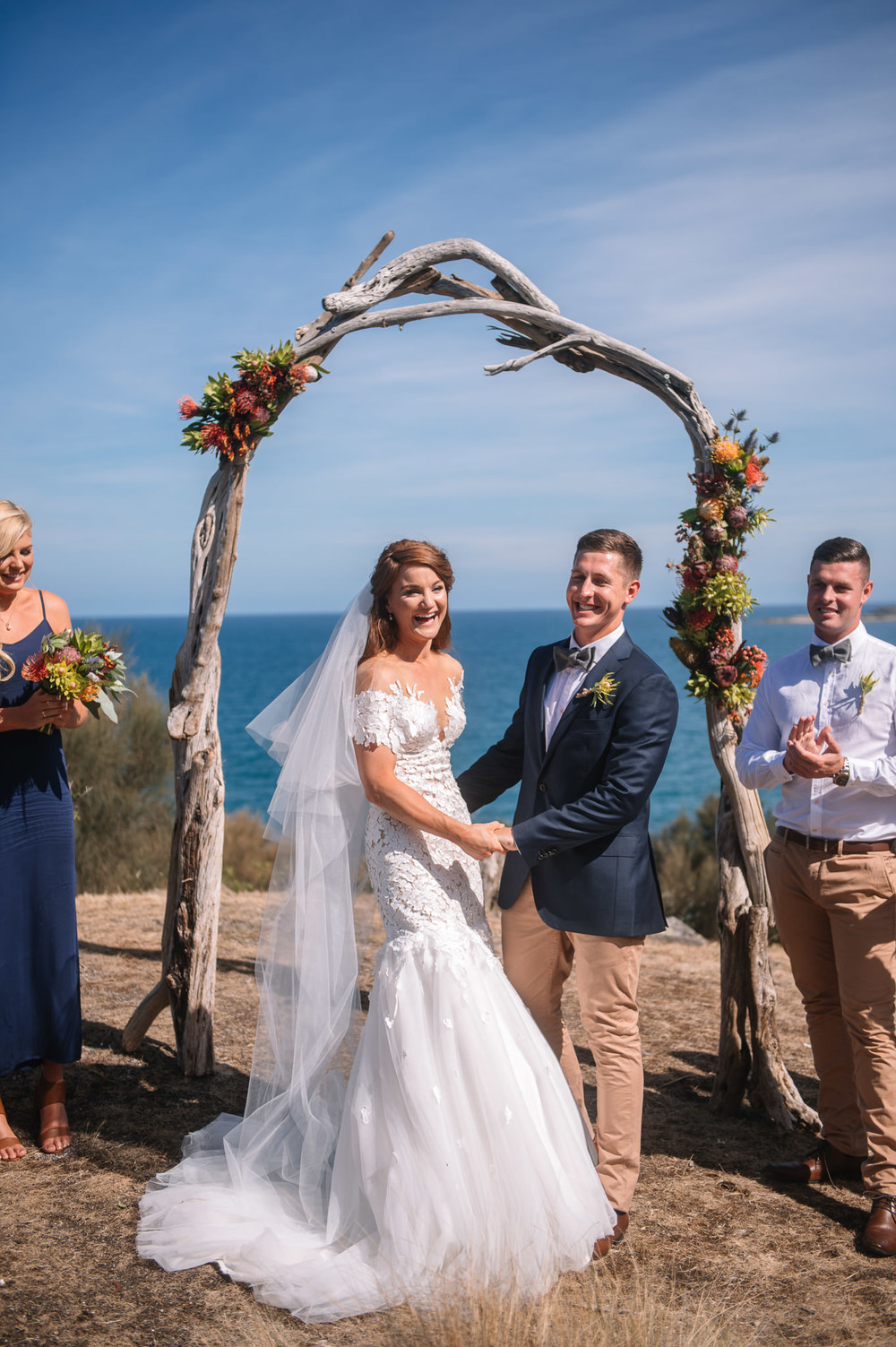 Coastal wedding under an arch of locally found driftwood