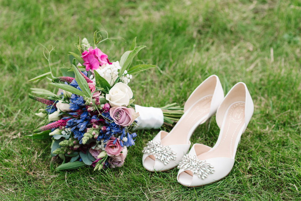 bride's shoes and wedding bouquet on grass