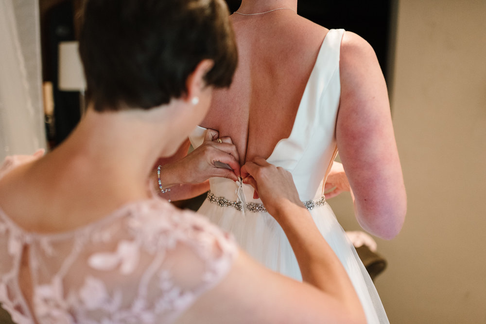 bridesmaid zipping up bride's dress in hotel room