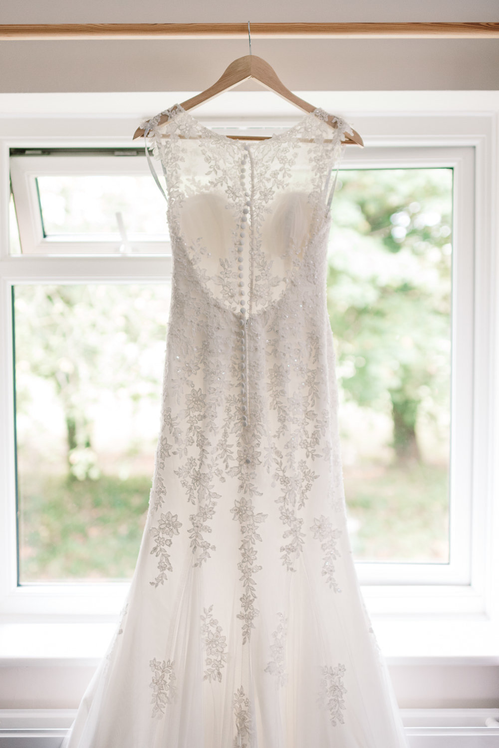 bride's lacey white wedding dress hanging on hanger on curtain rail in window
