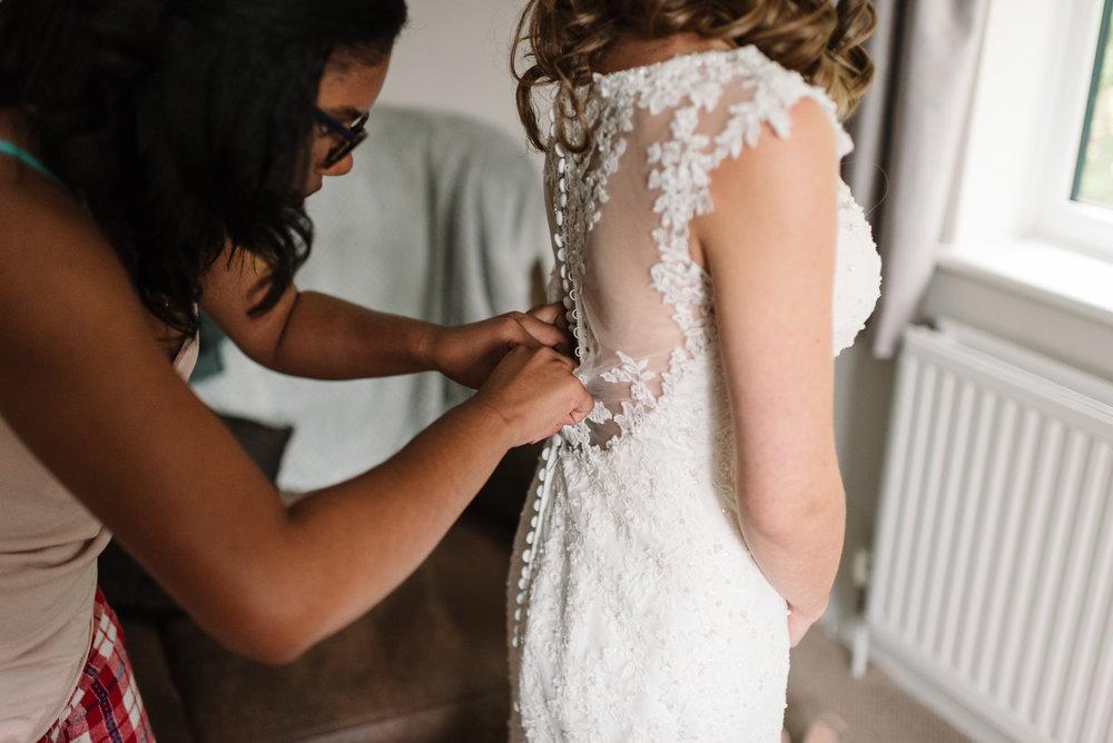bridesmaid doing up bride's dress