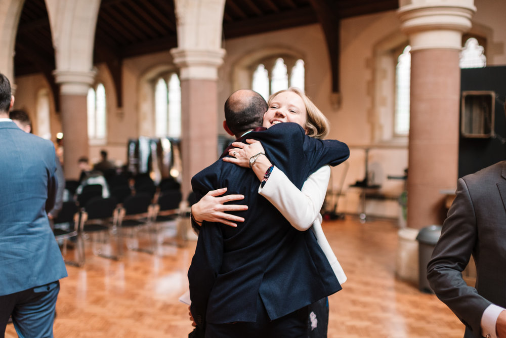 guests hugging before wedding ceremony at st saviour's church in guildford