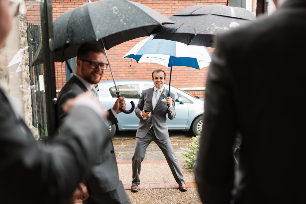 ushers with umbrellas at a rainy wedding