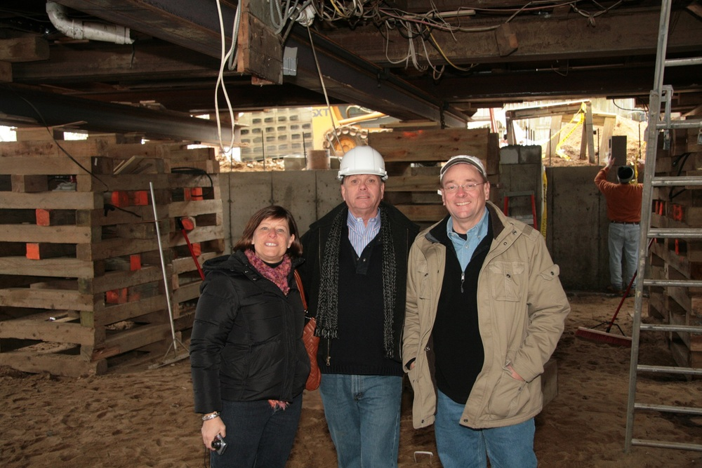 Brave clients stand below their lifted house with Fred Ambrose (center).