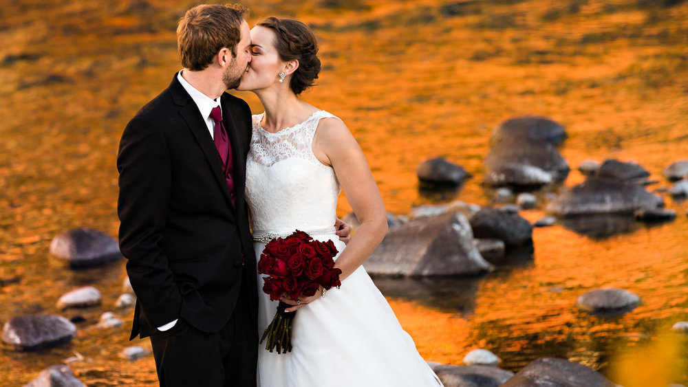 absaroka-beartooth-wilderness-montana-wedding-reception-couple-kissing-along-orange-fall-river.jpg
