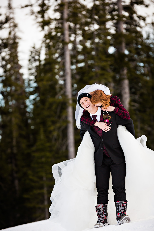 big-sky-montana-winter-wedding-breanna-formals-bride-jumps-on-grooms-back.jpg