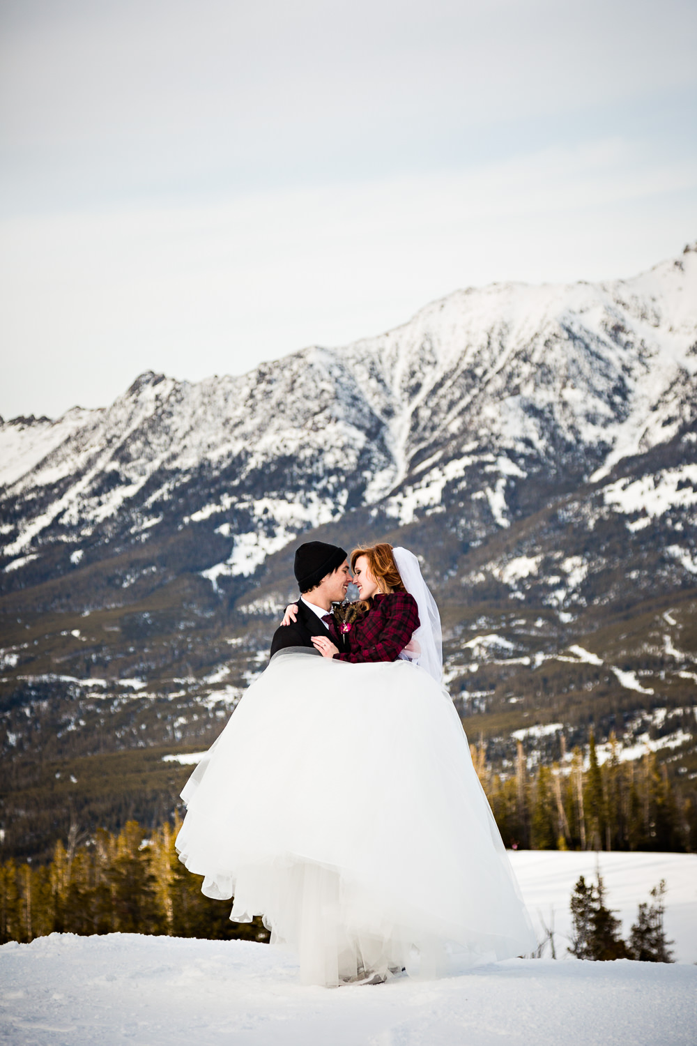big-sky-montana-winter-wedding-breanna-formals-groom-lifts-bride-for-kiss.jpg