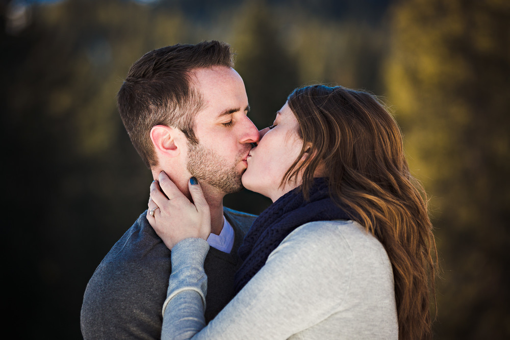 big-sky-montana-winter-engagement-session-couple-kissing-in-forest.jpg