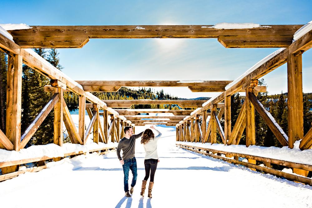 big-sky-montana-winter-engagement-session-couple-dancing-on-bridge.jpg