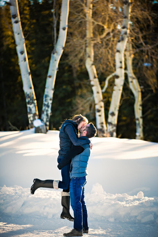 big-sky-montana-winter-engagement-session-couple-kissing-near-aspen-trees.jpg