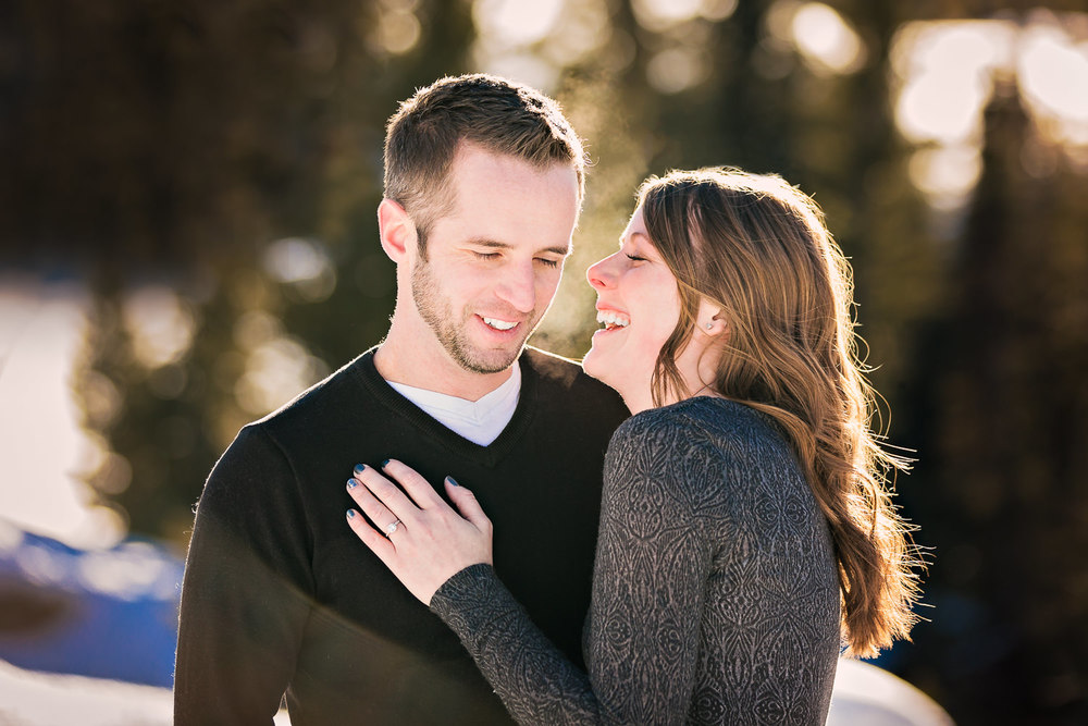 big-sky-montana-winter-engagement-session-couple-laughing in forest.jpg