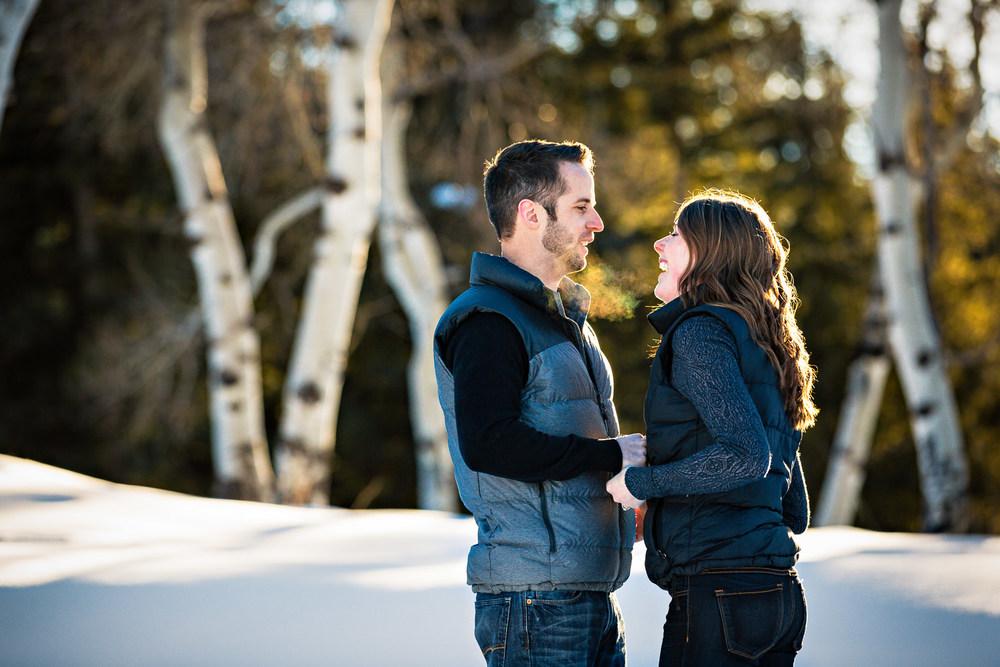 big-sky-montana-winter-engagement-session-couple-laughing-near-aspen-trees.jpg
