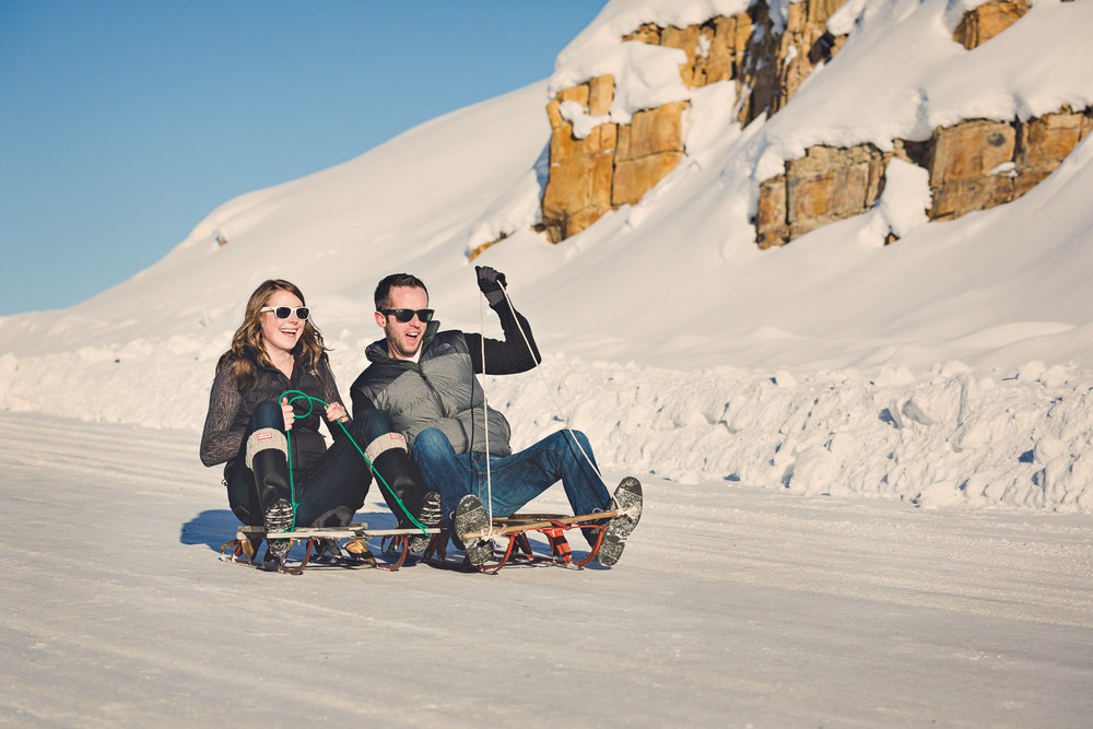 big-sky-montana-winter-engagement-session-couple-sledding.jpg