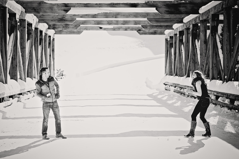 big-sky-montana-winter-engagement-session-couple-throwing-snowballs.jpg
