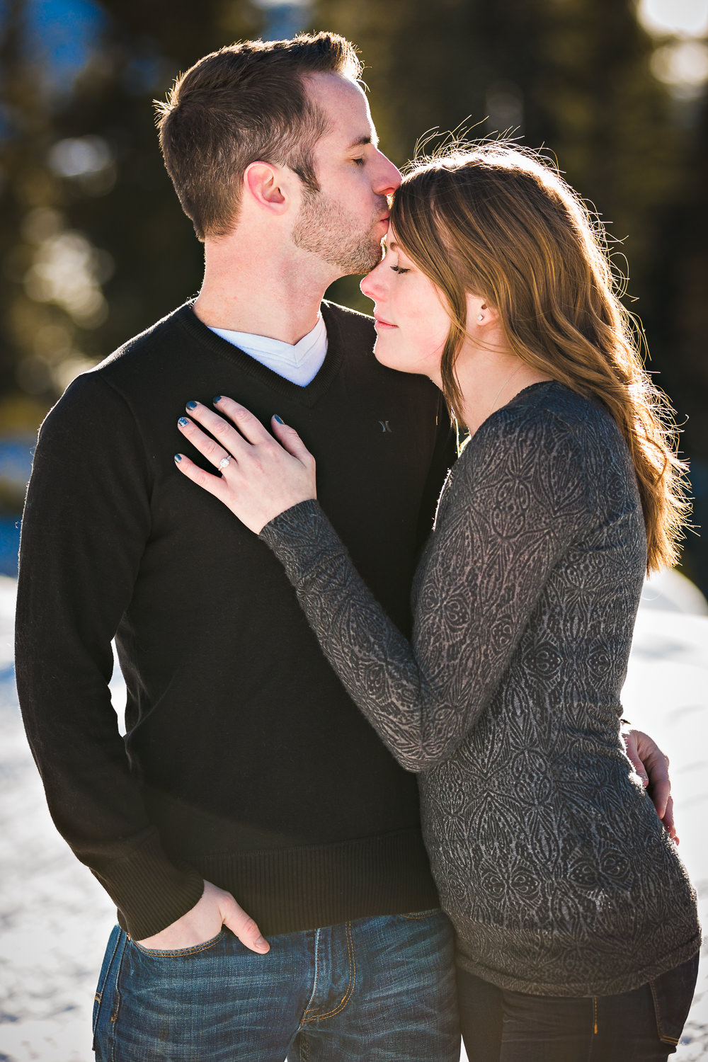 big-sky-montana-winter-engagement-session-man-kisses-womans-forehead.jpg