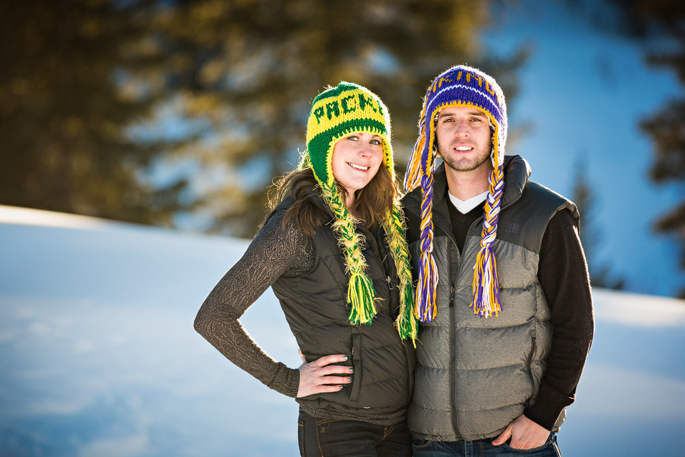 big-sky-montana-winter-engagement-session-couple-smiling-with-football-hats.jpg