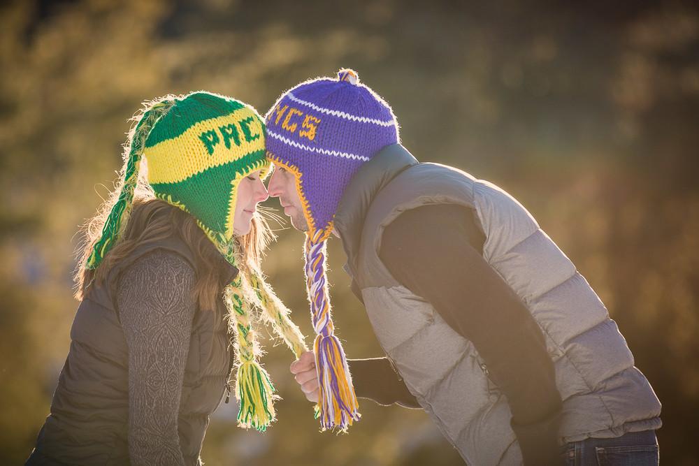 big-sky-montana-winter-engagement-session-man-tugs-on-womans-hat.jpg