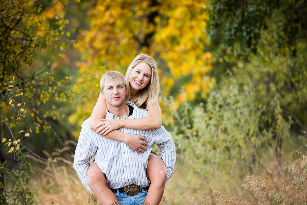 Billings-Montana-fall-engagement-man-gives-woman-piggyback-ride.jpg