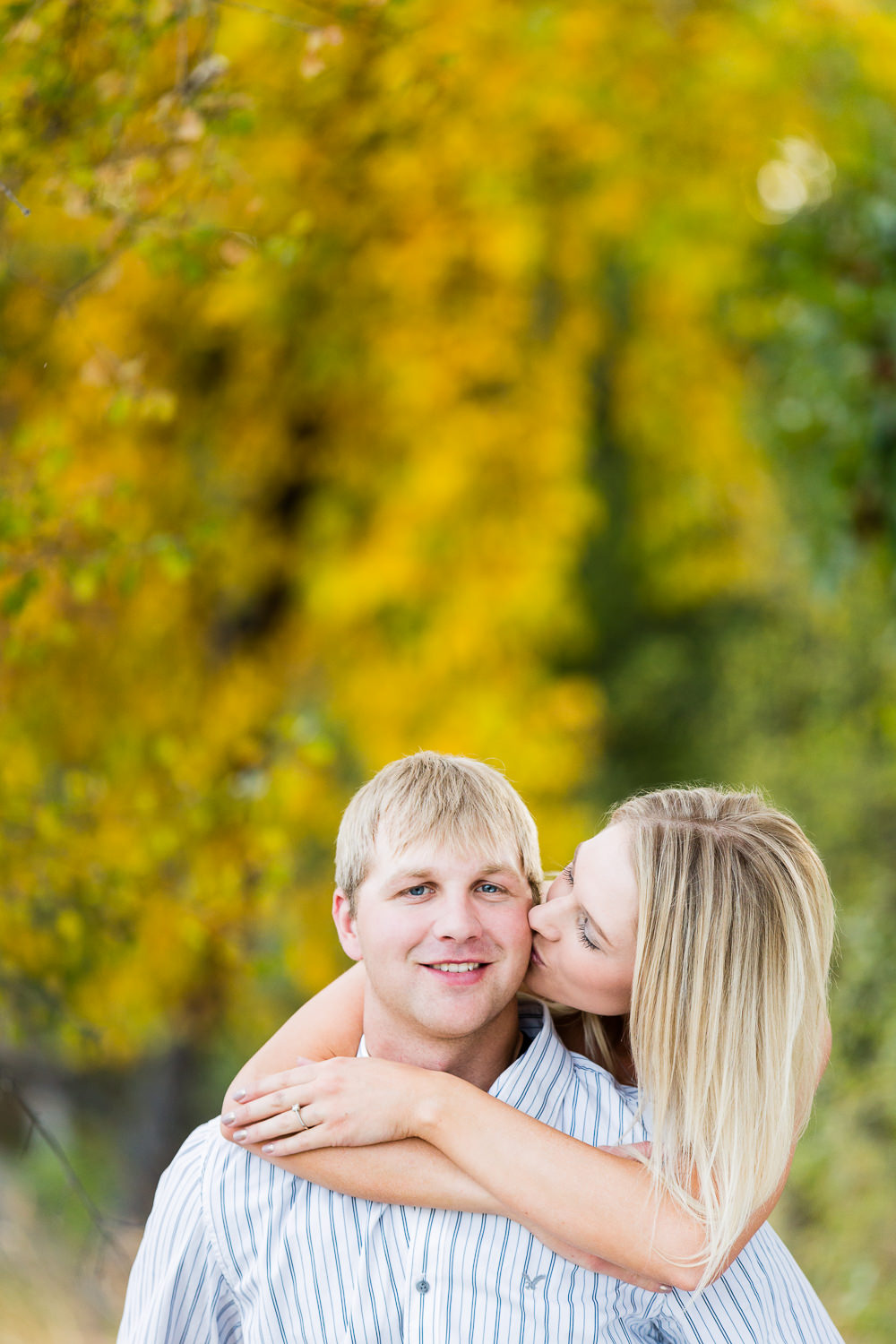 Billings-Montana-fall-engagement-woman-kissing-man's-cheek.jpg